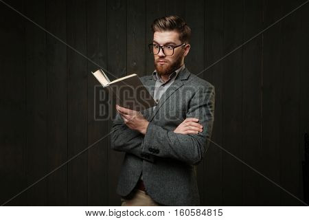 Portrait of amazed casual man in eyeglasses reading book isolated on the black wooden background