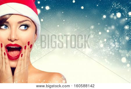 Christmas Girl. Beauty model woman in Santa Claus hat with red lips and manicure looking left with a surprised expression. Closeup portrait over winter snow wide background with copy space. Sales.