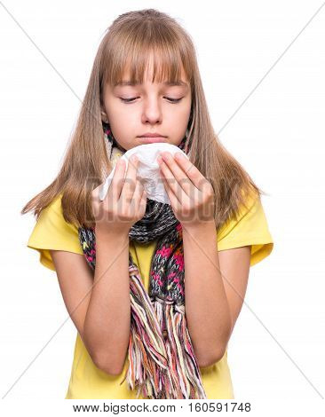 Healthcare and medicine concept - ill little girl with flu blowing nose. Kid wipes a nose a napkin. Child wearing yellow t-shirt and scarf.