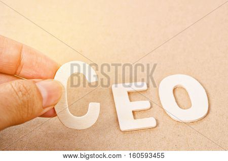 Hand arrange wood letters as CEO word on wood background.