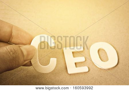 Hand arrange wood letters as CEO word on wood bakcground.