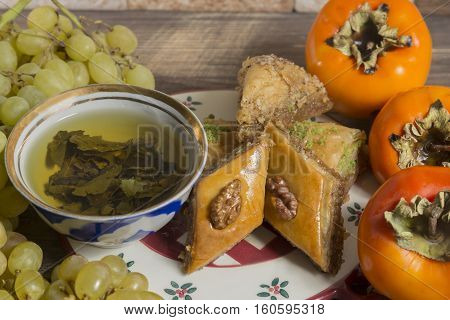 Eastern breakfast. Green tea with sweeties persimmons grapes against stone background.