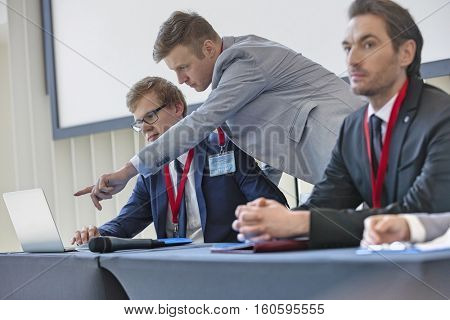 Businessman explaining strategy to colleague on laptop in convention center