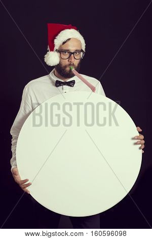 Handsome young hipster guy having fun at New Year's party wearing Santa's hat and holding a blank cardboard circle