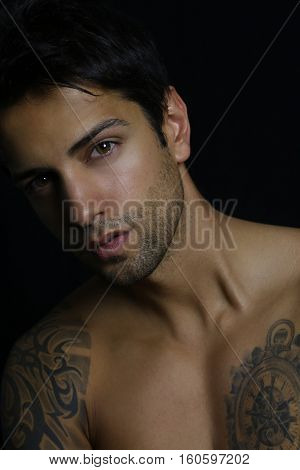 Close up portrait of an handsome young man on black background