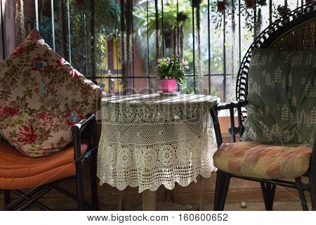 Knitted Tablecloth On Table, Cushion And Pillow On Rattan Chair In Living Room