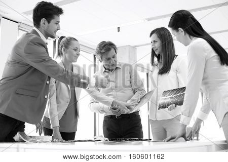 Male design professional with team discussing at table in new office