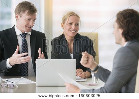 Confident middle aged business man in formal wear explaining his ideas to a client or business partner at meeting, trying to convince, discussing proposal, interviewing vacancy applicant