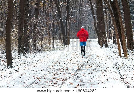Athlete man runner running at winter time in city park or forest. Runner jogging in snow. Outdoor sport and fitness concept. Active lifestyle