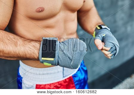 Close up of fit man wearing bandage on his hand. Nude torso