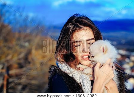 pretty girl young beautiful woman in fur waistcoat and scarf holds cute small dog pet in hands outdoors on blue sky