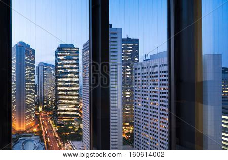 modern buildings in midtown of tokyo at twilight from glass window