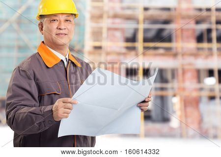 old asian man engineer with blueprint and new construction site