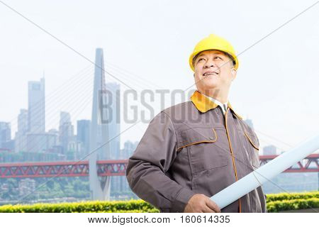 old asian man engineer with blueprint and bridge in modern city