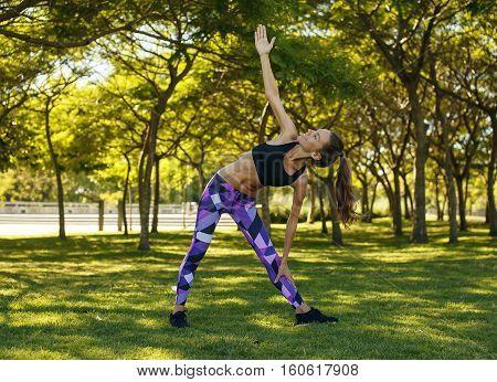 Beautiful happy girl doing yoga trikonasana pose in the sunny park summer day