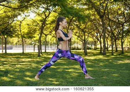 Beautiful caucasian girl doing yoga outdoors in the park summer day healthy lifestyle harmony asana.
