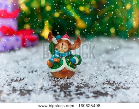 Ceramic Christmas toy elk in festive clothes standing in the snow the snow on top of throws blurred background with bokeh