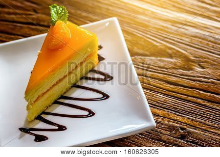piece of orange cheese cake in the white plate on the brown bark background