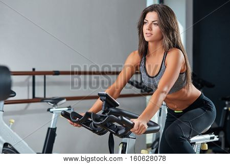 Muscular young woman working out on the exercise bike at the gym, intense cardio workout. She is smiling and looking ahead