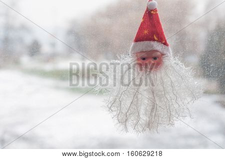 Winter window decorated with the head of Santa Claus