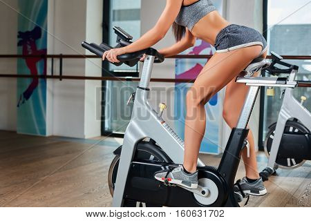 Young female feet exercising and pedaling a stationary bicycle in the fitness center