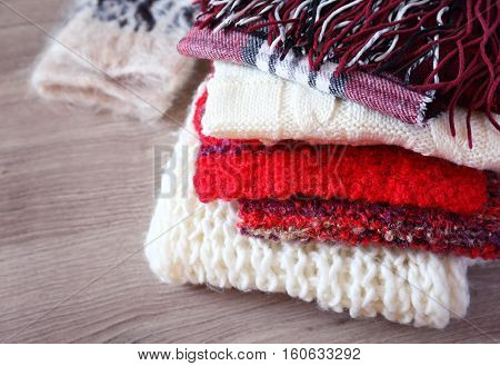 Preparation for winter: Pile of warm knitted woolen scarves and mitten are folded in one heap