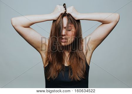 Studio shot of young pretty woman falling into despair and clutching her head isolated on grey background.
