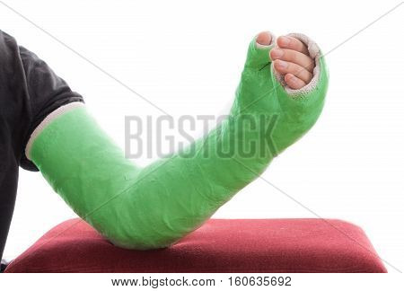 Green Long Arm Plaster / Fiberglass Cast Resting On Ottoman
