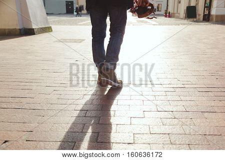 The traveler walks through the old town with a camera in hand. Travel concept