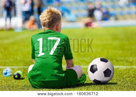 Young Soccer Football Player. Little Boy Sitting on Soccer Pitch. Youth Football Player in Green Soccer Jersey