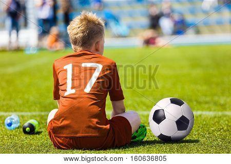 Young Soccer Football Player. Little Boy Sitting on Soccer Pitch. Youth Football Player in Orange Soccer Jersey