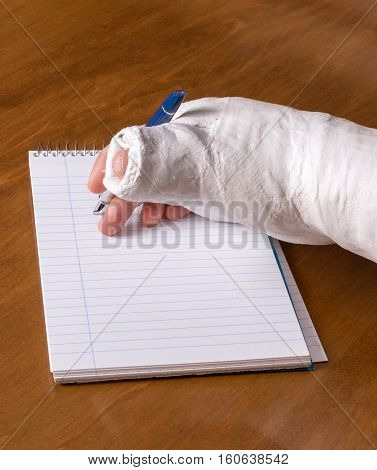 Person With An Arm Cast Writing A Note