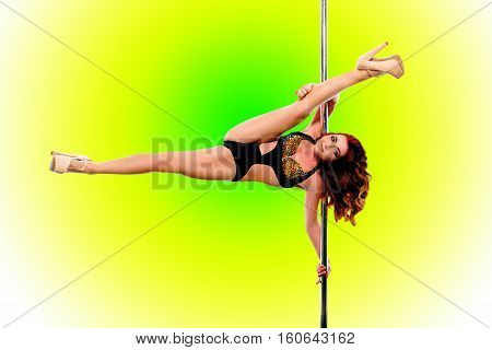 Young red hair woman in high heels shoes on pylon on colorful background