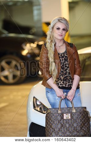 MOSCOW - MAY 20, 2016: Woman (with model release) stands near sport car with bag Louis Vuitton. French Louis Vuitton fashion house founded in 1854