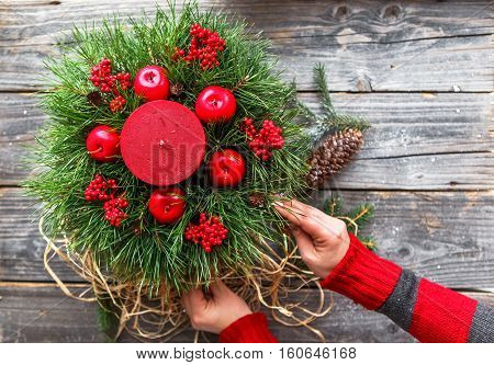 Girl in a red sweater decorate a candle with using pine tree branch. Hands packing Christmas gift on wood background top view