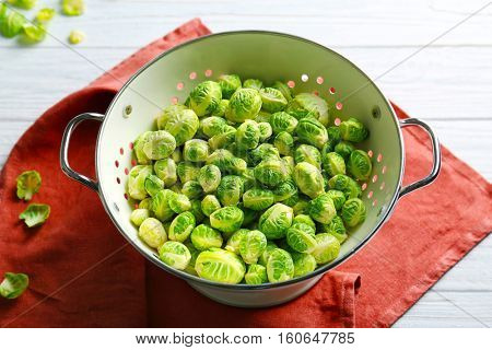 Brussels sprouts in colander on table