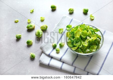 Brussels sprouts in a glass bowl and napkin on grey table