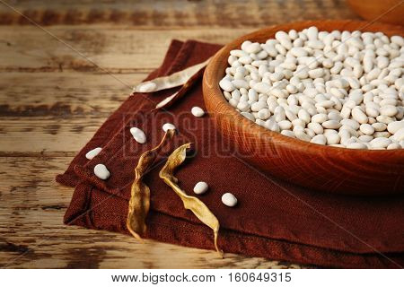 Bowl with white haricot beans and napkin on wooden table