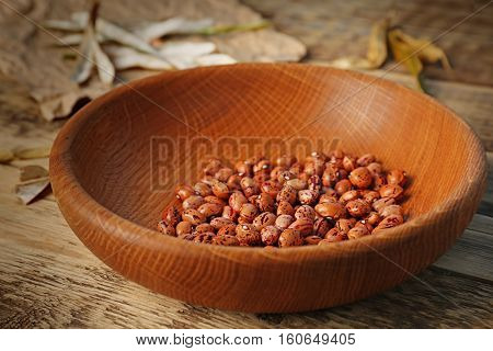 Bowl with brown haricot beans on wooden table