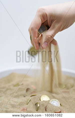 Abstract composition of spending money. Woman hand with coins and sand.