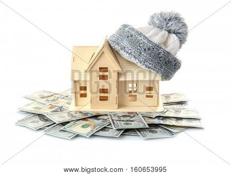 Plywood toy house with warm hat and dollars, isolated on white