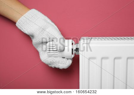 Female hand in warm mitten on temperature regulator of heating battery on pink background, closeup