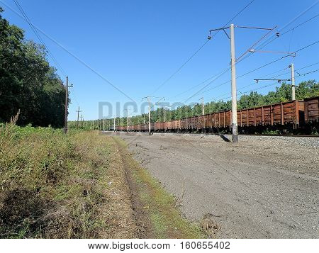 Freight train consisting of a gondola rides on the stretch.