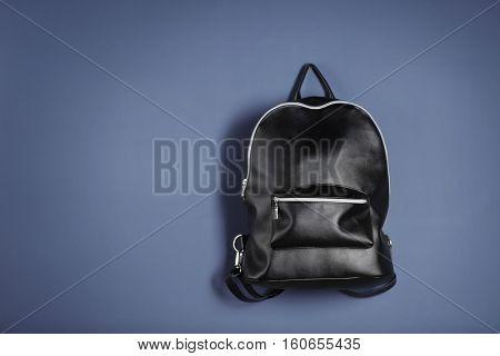 Black leather rucksack on dark background