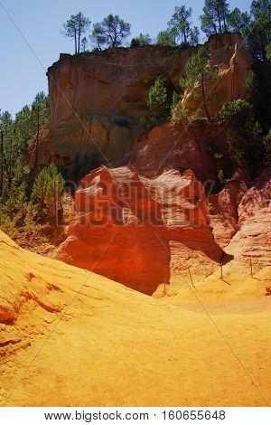 Orange ochre picturesque hills. Village Roussillon Luberon Provence France. Preserve natural dye production - ocher.