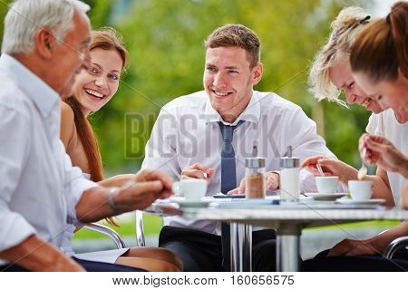 Successful group of businesspeople having meeting in a coffee shop outdoors