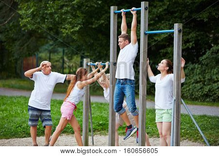 Group doing fitness training together in nature at horizontal bars