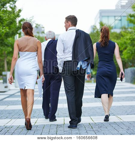 Business people from behind walking together to their destination