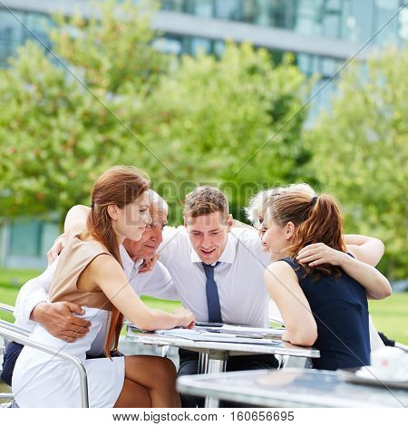 Business team hugging for motivation in a meeting outdoors