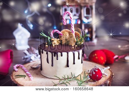 Homemade cake decorated with Christmas gingerbread men, waffles and candy canes on a rustic wood stand